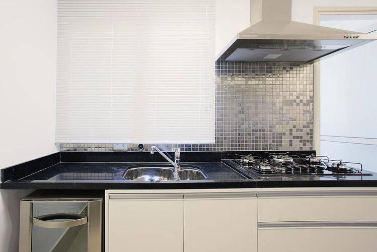 Cozinha compacta com balcão de granito preto e pastilhas prateadas Projeto de Sesso Dalanezi