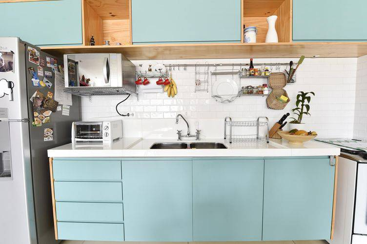 Cozinha compacta com armários azuis e metro white Projeto de Carla Cuono