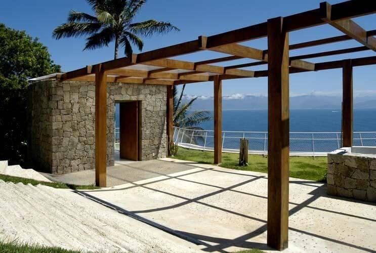 Estrutura com pergolado de madeira e parede de pedra Projeto de Enrico Benedetti