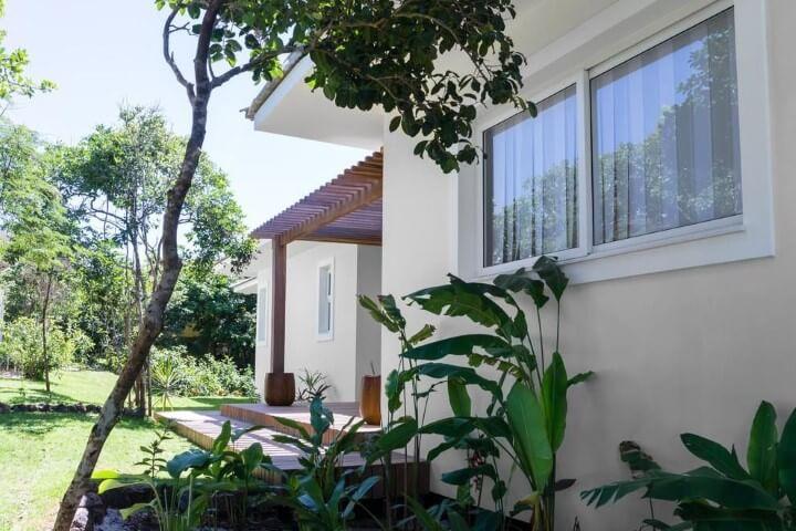 Pergolado de madeira entre duas partes da casa Projeto de Renata Matos