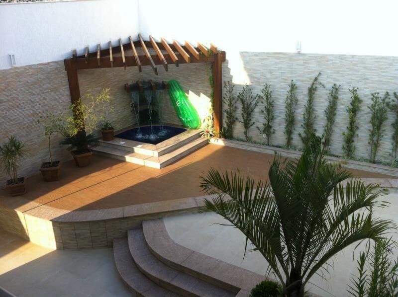 Pergolado de madeira sobre piscina pequena com cascata Projeto de Solange Figueiredo