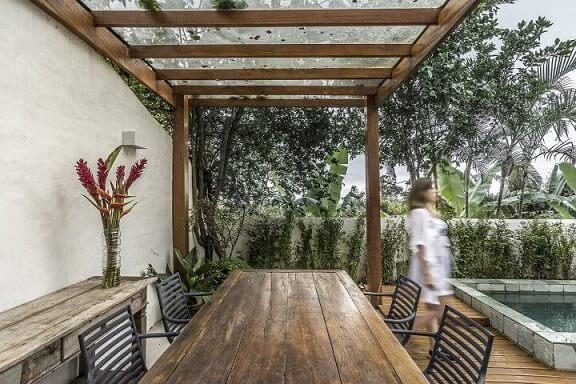 Varanda com pergolado de madeira e mesa de jantar com material combinando Projeto de Paulo de Camargo