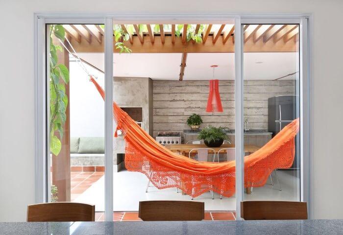 Varanda com pergolado de madeira e rede laranja Projeto de Antonio Armando de Araujo