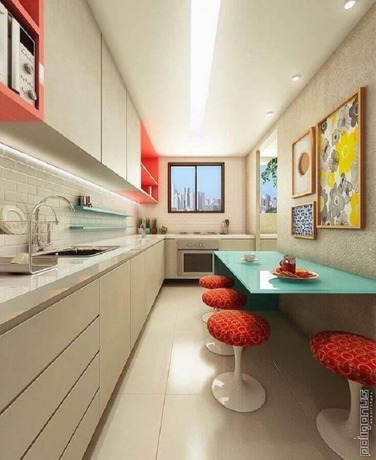 cozinha pequena planejada com mesa azul e banquetas vermelhas