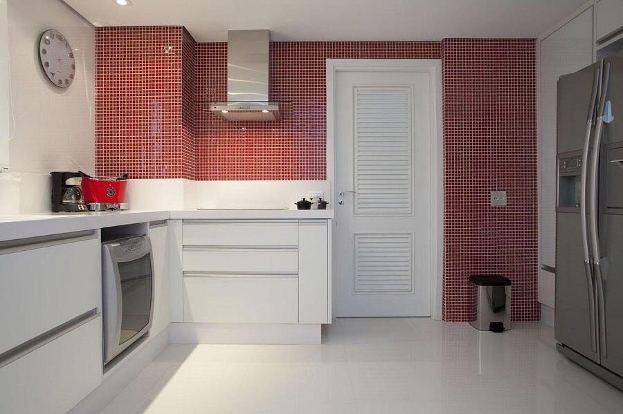 Cozinha branca com pastilhas vermelhas.