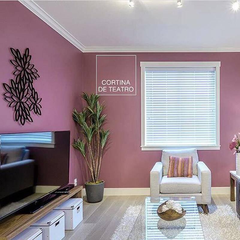 Sala na cor rosa cortina de teatro com cortina branca e poltrona branca.