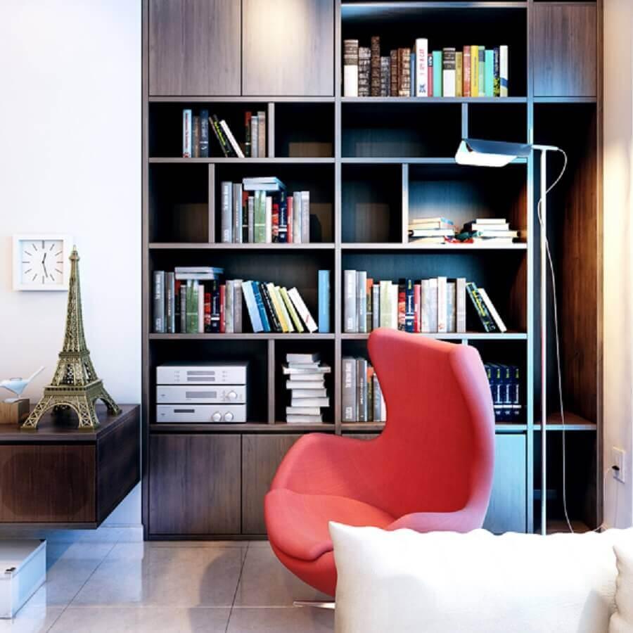 cantinho da leitura na sala decorado com estante de madeira e poltrona egg Foto V-Consultancy