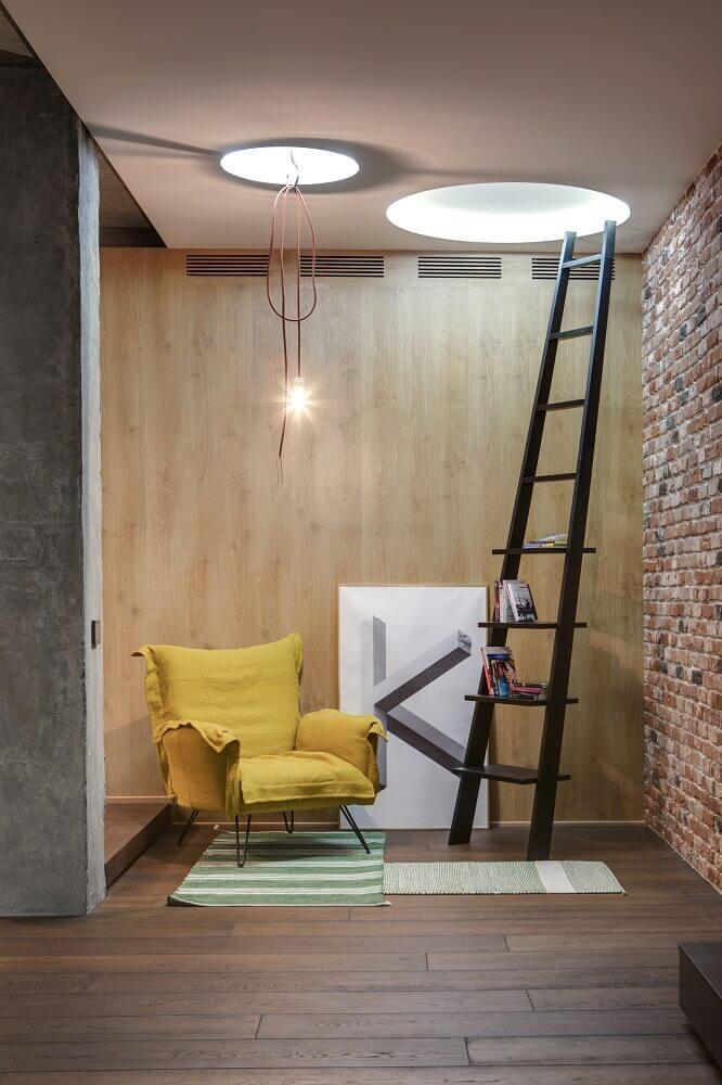 escada de madeira como estante para cantinho da leitura com parede tijolinho e poltrona amarela Foto Behance