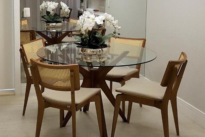 Mesa redonda de vidro com 4 cadeiras e espelho na parede Projeto de Tatiana Baroni