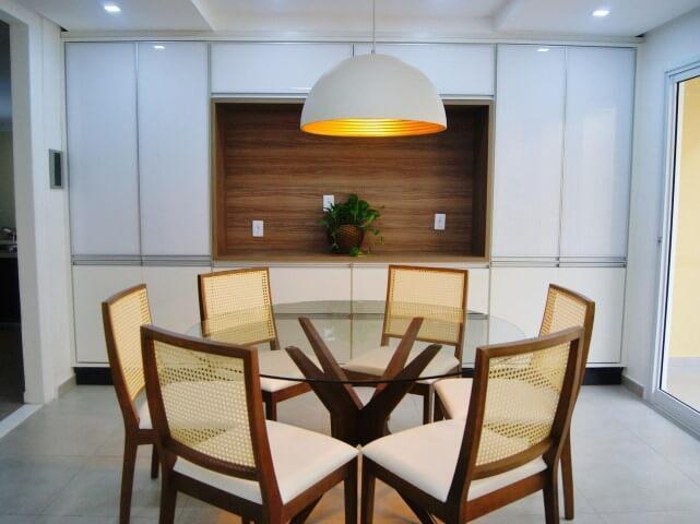 Mesa redonda de vidro com 6 cadeiras e luminária arredondada Projeto de Priscila Fernandes