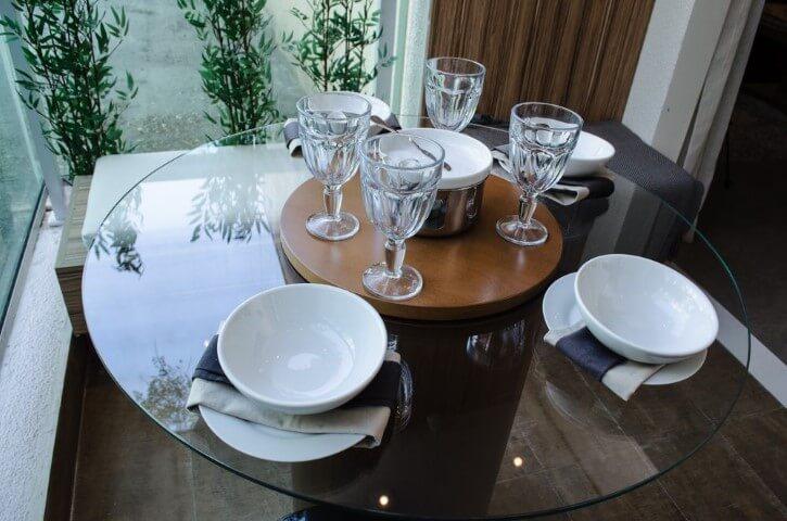 Mesa redonda de vidro e banco com almofada branca Projeto de Studio Ecoara