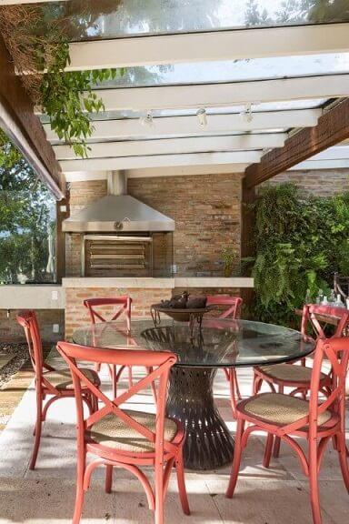 Mesa redonda de vidro e cadeiras vermelhas em ambiente externo Projeto de Kali Arquitetura