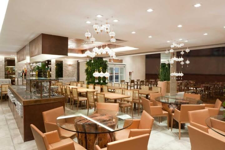 Restaurante com mesa redonda de vidro e mesa retangular Projeto de LF Rezende