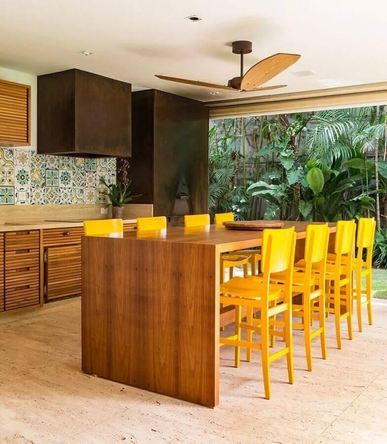 cores quentes para varanda gourmet com móveis de madeira e banquetas amarelas  Foto Marina Linhares Interiores
