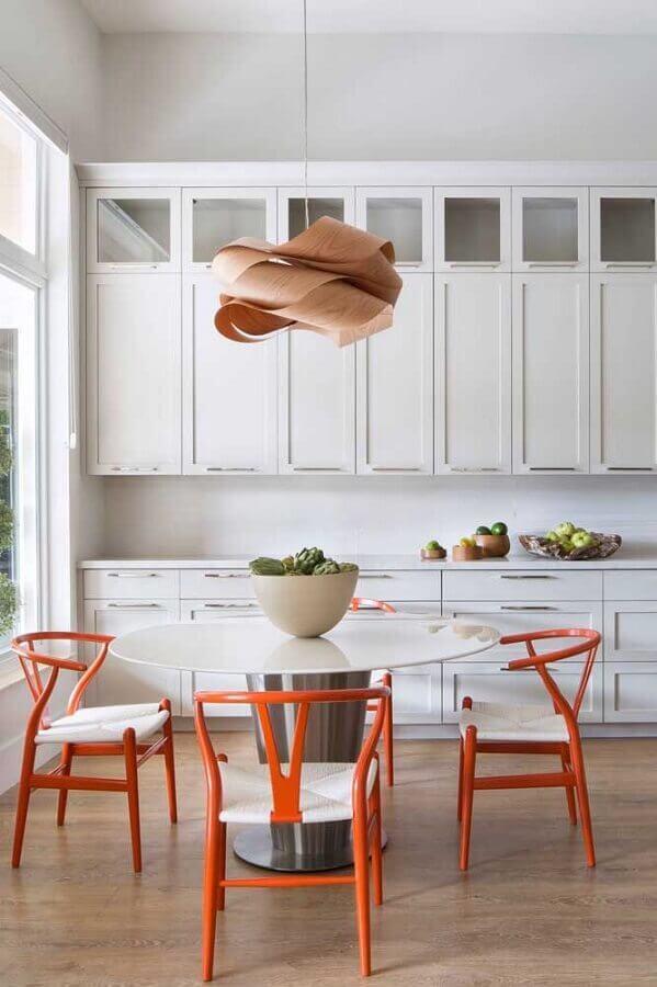 decoração de cozinha branca com cadeiras laranjas e mesa redonda  Foto Krista + Home