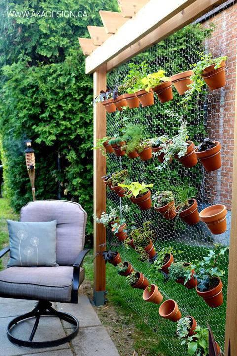 horta vertical com vasos de barro e tela