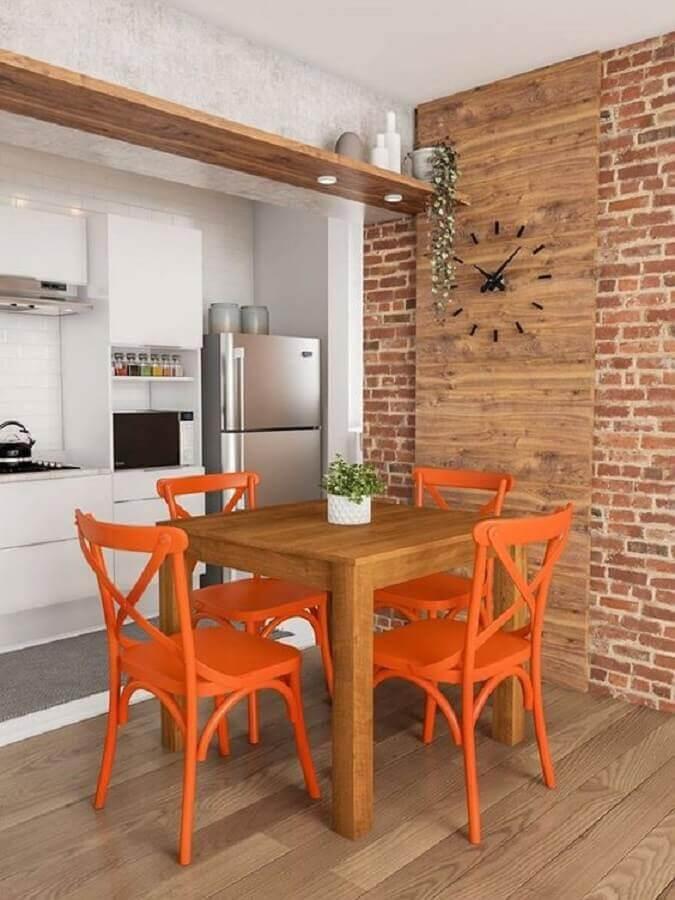 sala de jantar decorada com cadeiras laranja e parede de tijolinho Foto Histórias de Casa