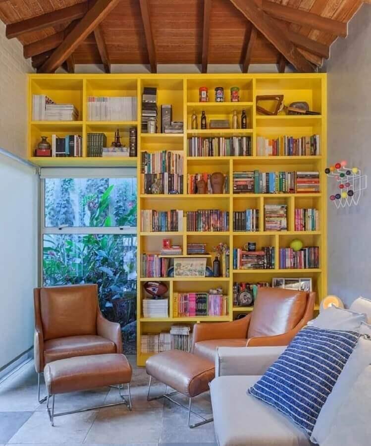 sala decorada com poltronas de couro e estante de nichos amarela  Foto Carmen Calixto Arquitetos