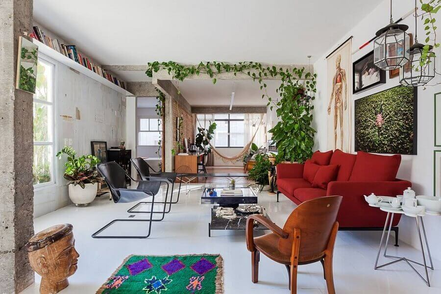 sofá vermelho para decoração de sala com muitas plantas e poltrona de madeira Foto Pinterest