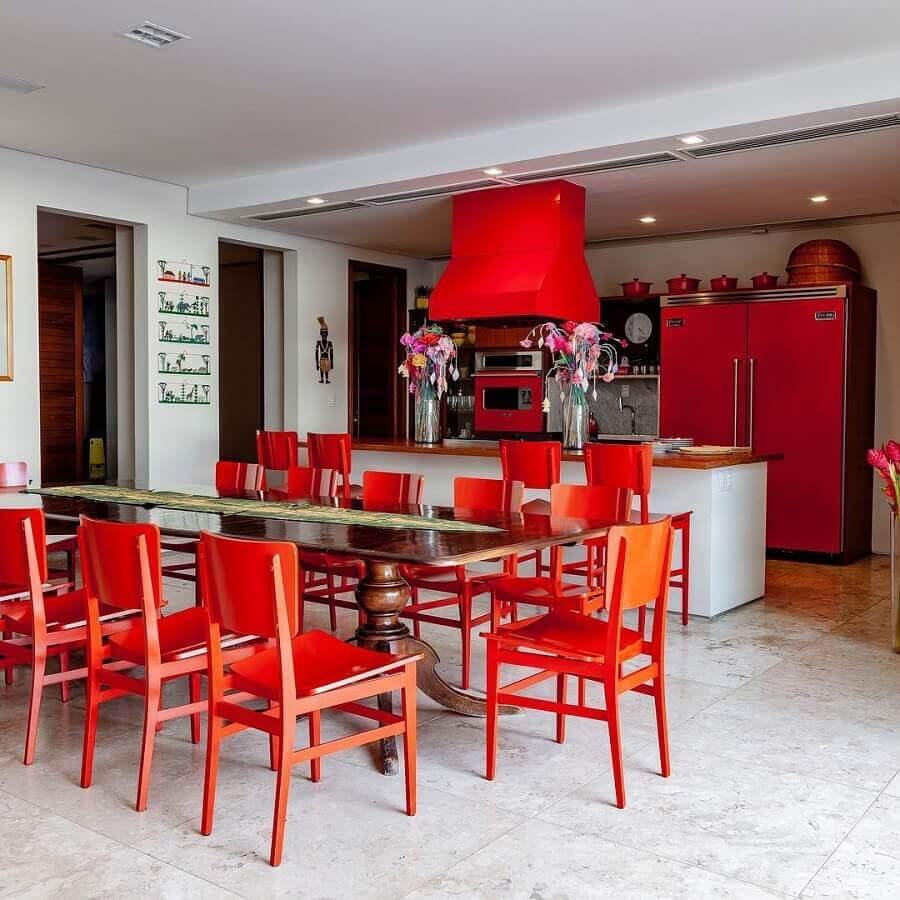 varanda gourmet decorada com cadeiras e armários vermelhos  Foto DB Arquitetos