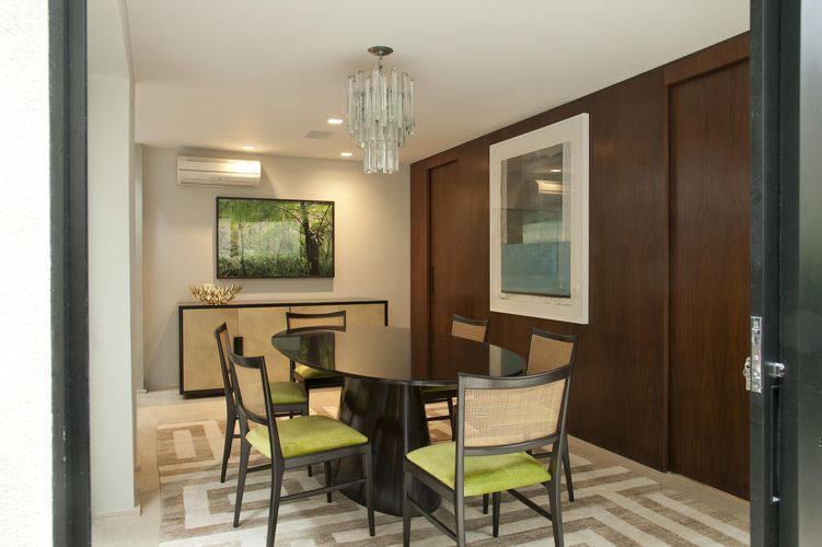 Mesa de Jantar na cor preta com tampo oval e cadeiras com detalhes verdes