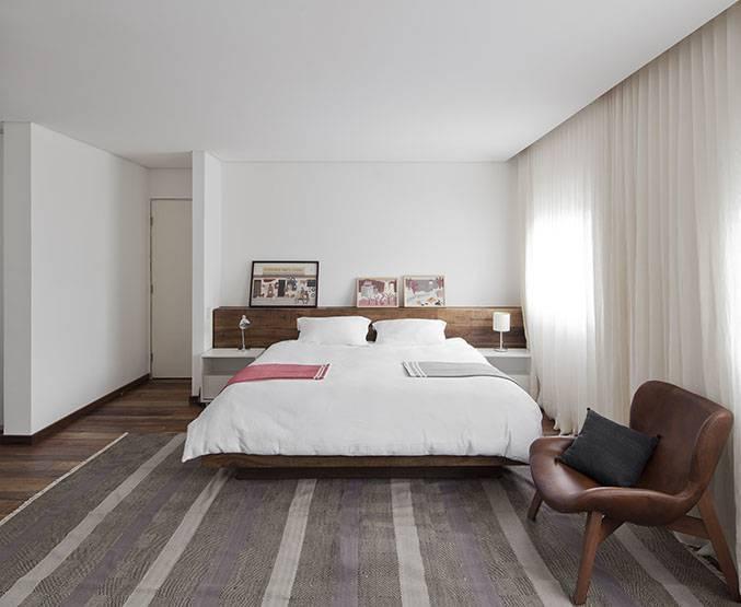 A integração de quartos fez com que a área de suíte aumentasse. O chão em madeira de demolição integra visualmente os ambientes.