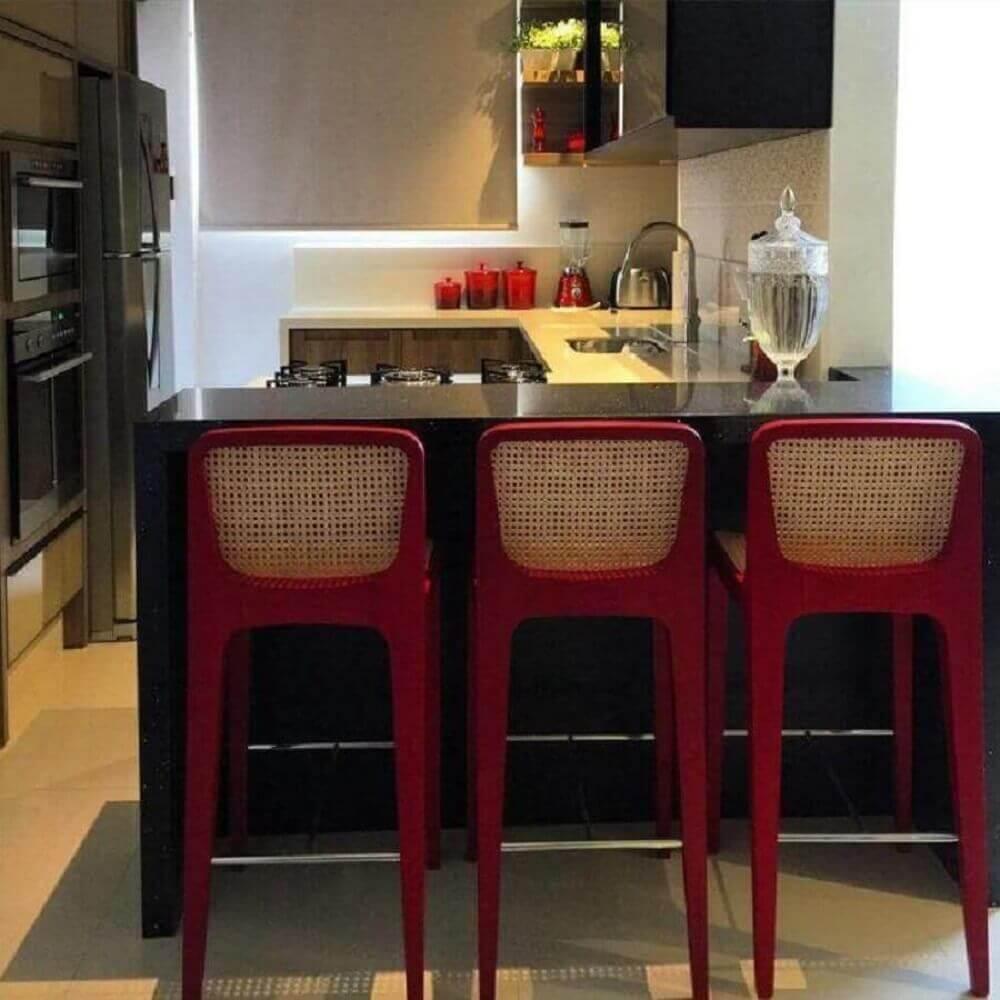 Balcão de cozinha feito em granito preto e banquetas vermelhas