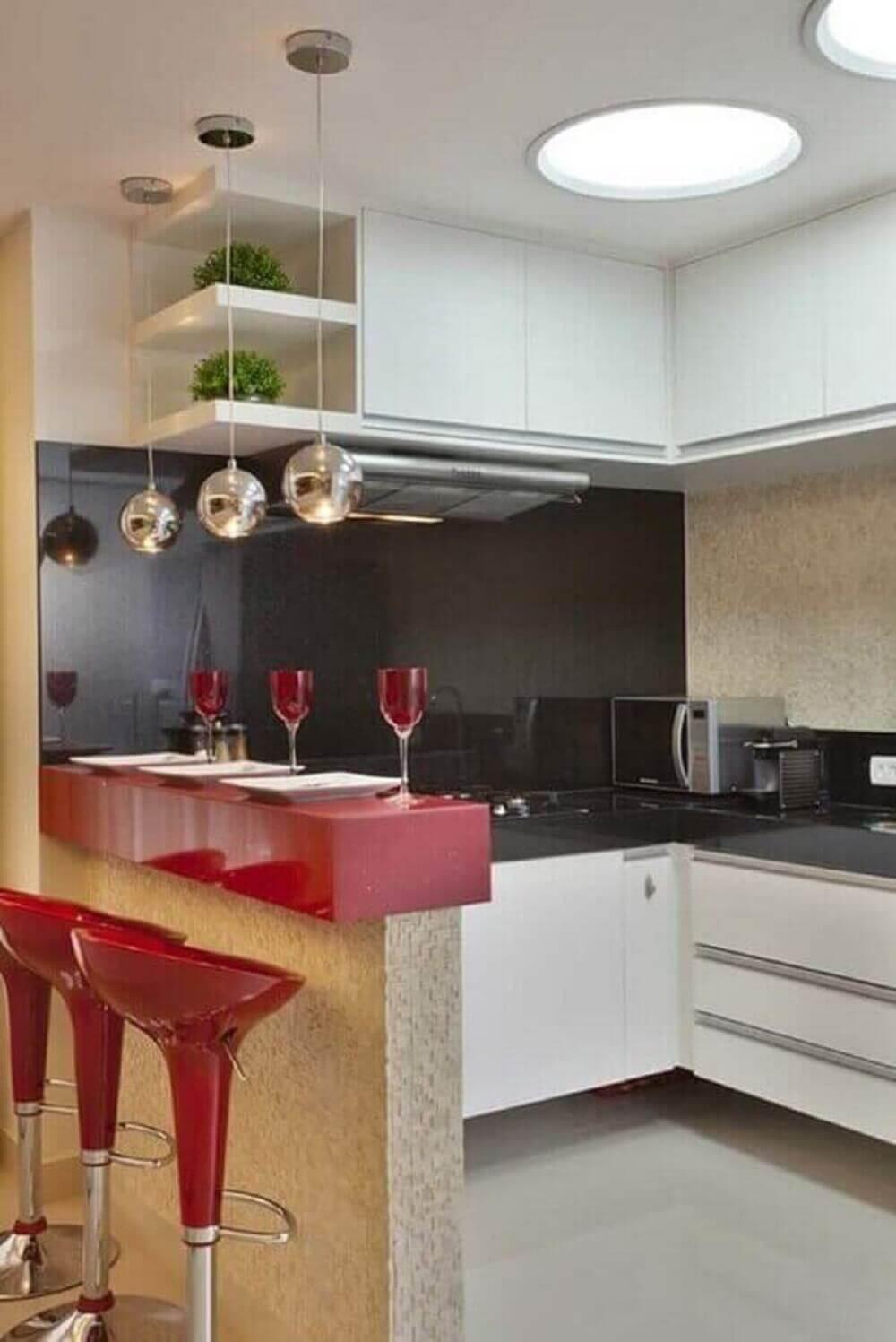 Balcão de cozinha pequeno em tom de vermelho e pendentes metálicos