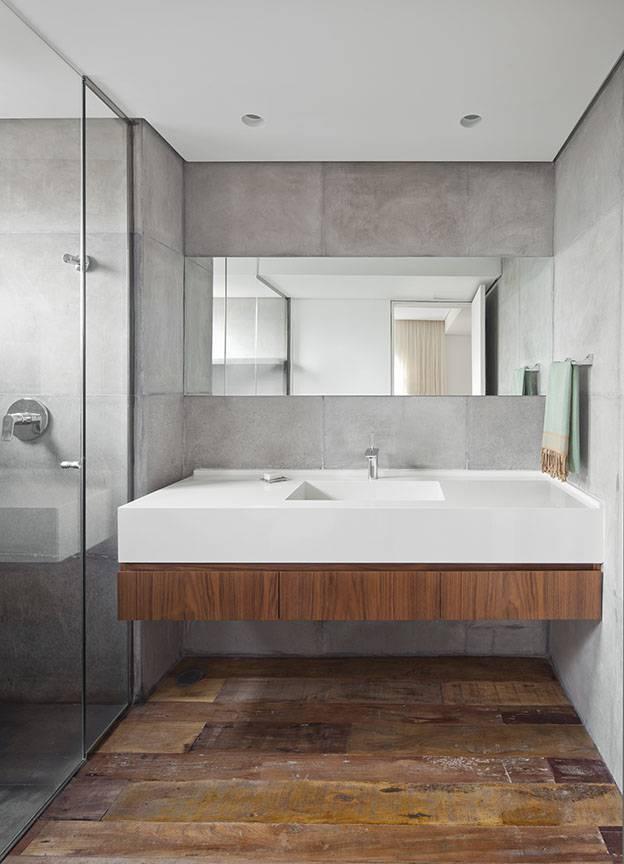 No banheiro do apê decorado pela dupla do Meireles + Pavan Arquitetura, o sóbrio está nas cores do revestimento de madeira de demolição e no cimento queimado.