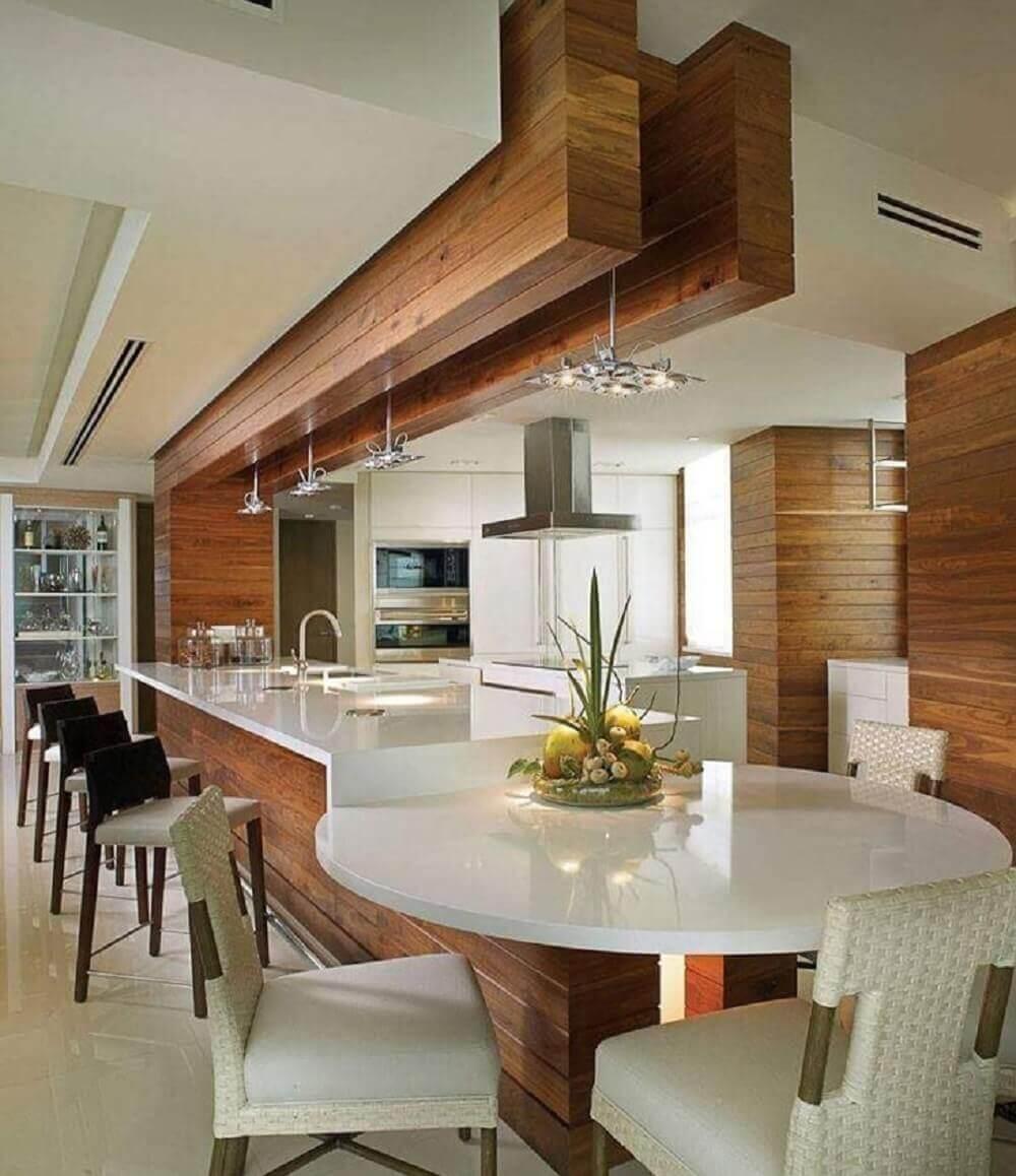 O balcão de cozinha começa retangular e termina com uma mesa redonda