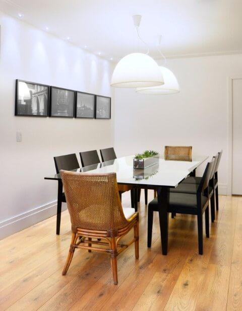 Sala de jantar com piso laminado e cadeiras diferentes Projeto de Coutinho Vilela