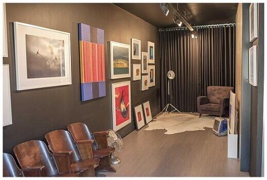 Sala moderna com piso laminado e obras de arte Projeto de Paula Ines Sizinando