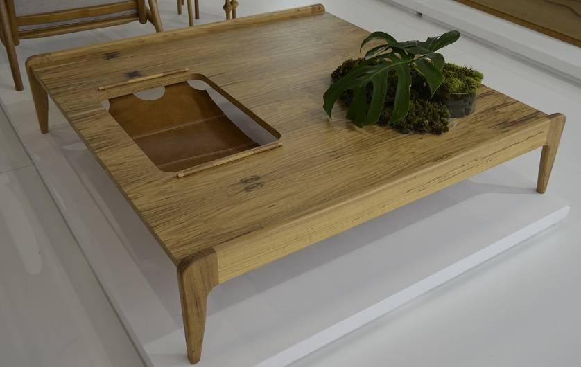 A mesa em madeira ganha um recorte com detalhe em couro para abrigar revistas e outros objetos, da Tissot.