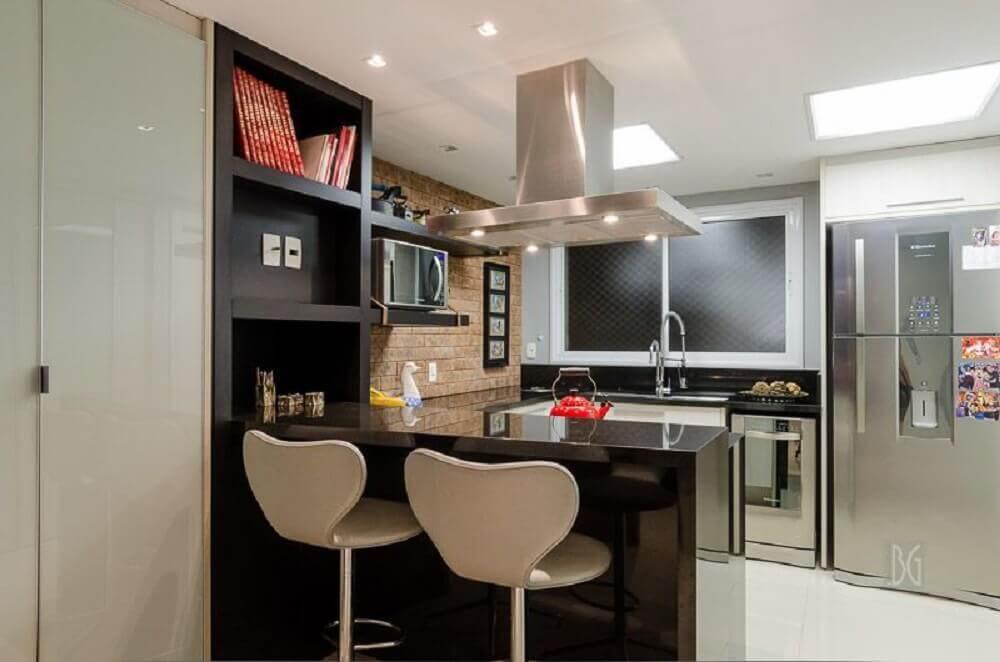 cozinha planejada com parede de tijolinho e balcão de cozinha preto.