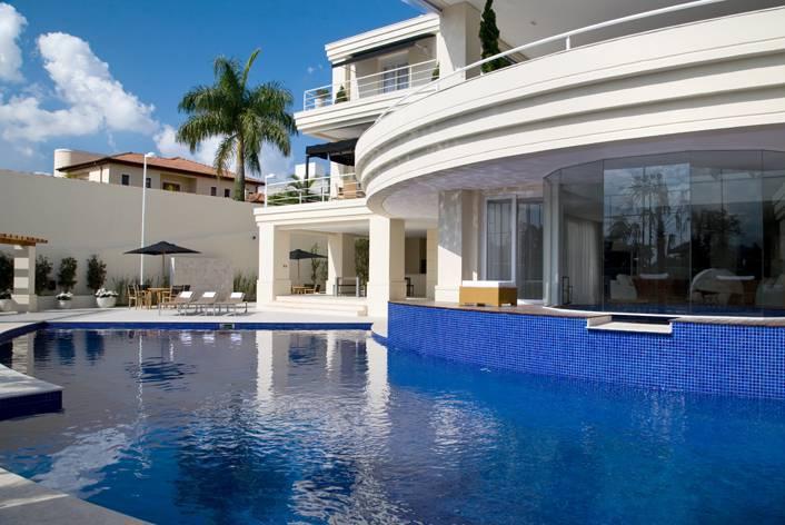 Área externa com piscina e fachada da casa do jogador de futebol Cafu.