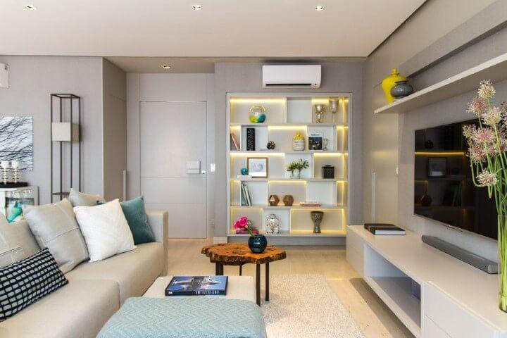 Sala de TV bege e estante com iluminação LED Projeto de Marilia Veiga