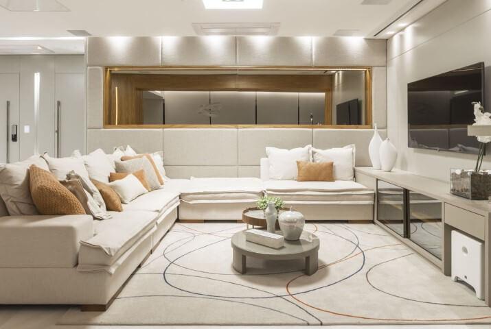 Sala de TV clara com almofadas combinando com o tapete Projeto de Red Square Arquitetura