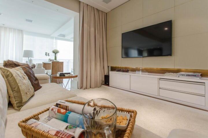 Sala de TV com TV fixada na parede Projeto de Márcia Ácaro