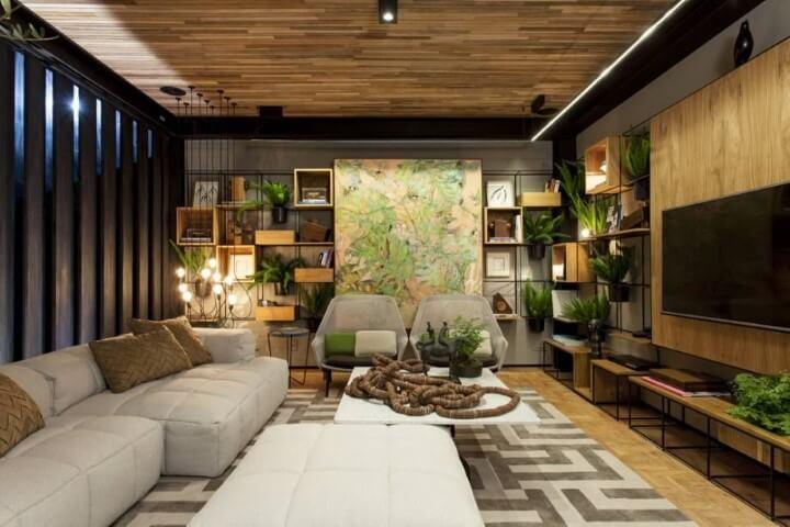 Sala de TV com estrutura metálica como estante e plantas Projeto de Casa Cor Bahia 2017