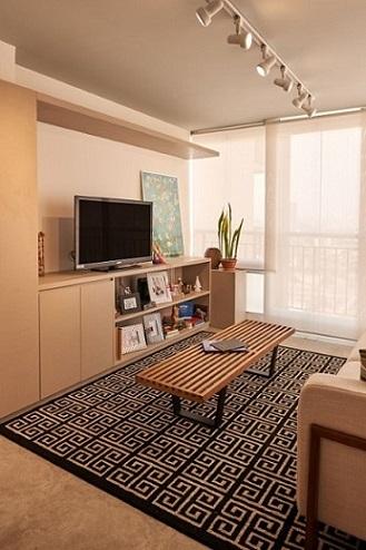 Sala de TV com mesa de centro de madeira e tapete geométrico Projeto de Go Up Arquitetura