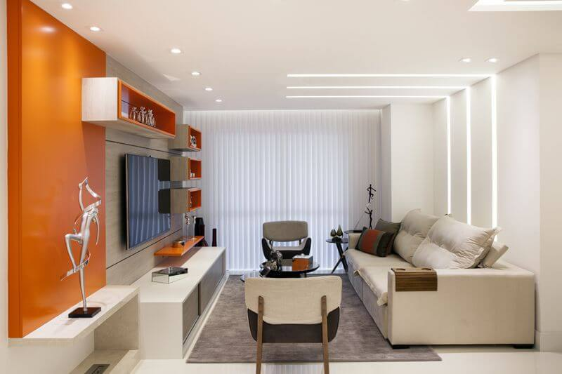 Sala de TV com objetos decorativos laranjas Projeto de Sueli Zapparolli