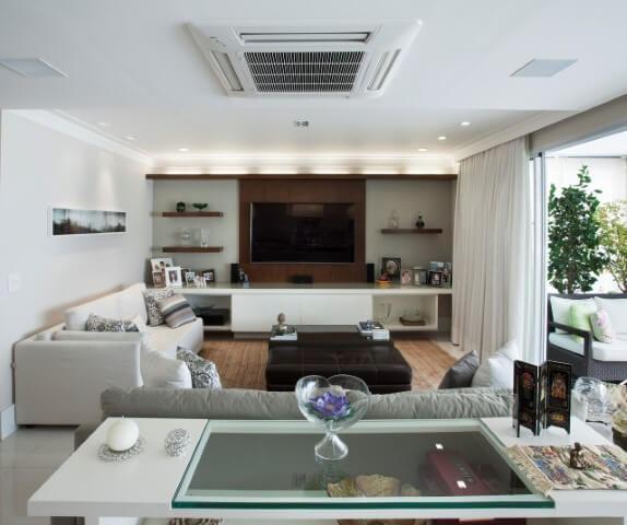 Sala de TV com painel de madeira com prateleiras similares Projeto de Katia Llaneli