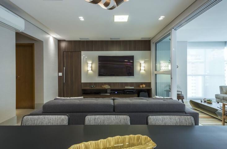 Sala de TV com painel de vidro branco e iluminação aos lados Projeto de Arquiteta Petini