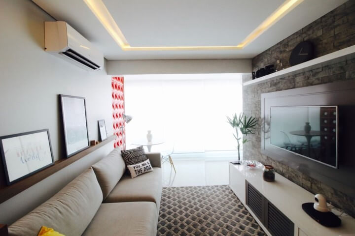 Sala de TV com parede de tijolos e prateleiras acima da TV e do sofá Projeto de Gláucio Gonçalves