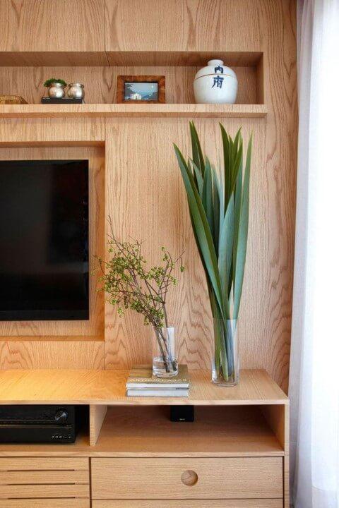 Sala de TV com parede revestida com madeira e rack do mesmo material Projeto de Coutinho Vilela