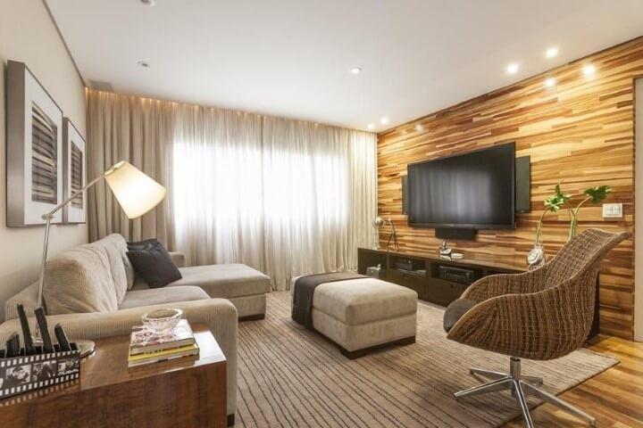 Sala de TV com parede revestida de madeira e móveis discretos