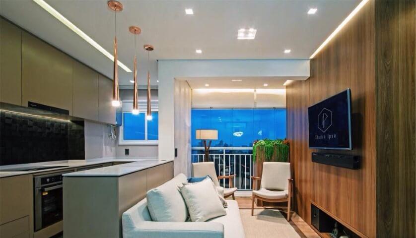 Sala de TV com parede revestida de madeira integrada à cozinha