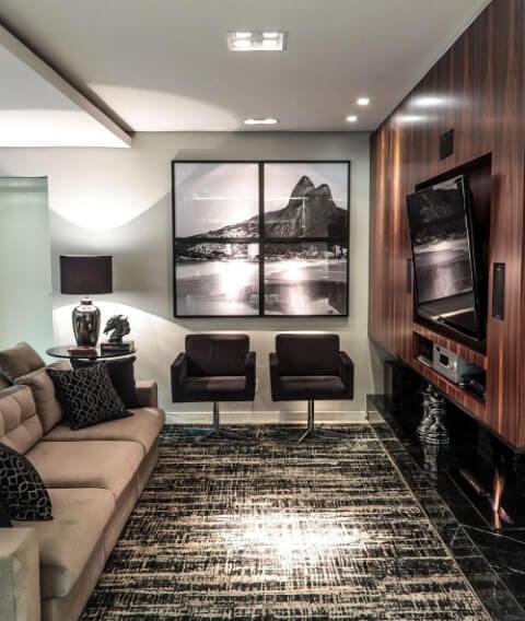 Sala de TV com parede revestida em madeira e TV adaptável Projeto de Pauline Feoni