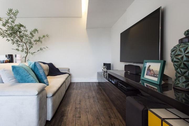 Sala de TV com sofá branco e chão de madeira rústica