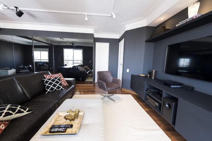 Sala de TV de parede escura e móveis idem Projeto de Carla Cuono